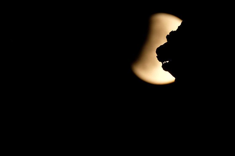 Скульптурный лев на фоне частичного лунного затмения на площади святого Марка в Венеции