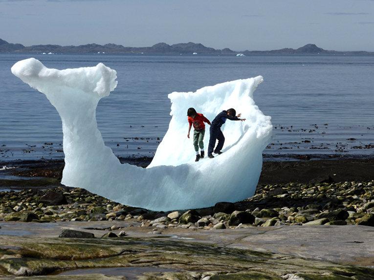 Дети играют с айсбергом в Нууке, Гренландия