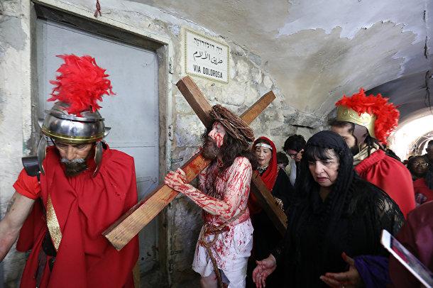 Паломники несут большой деревянный крест вдоль пути страданий в Иерусалиме