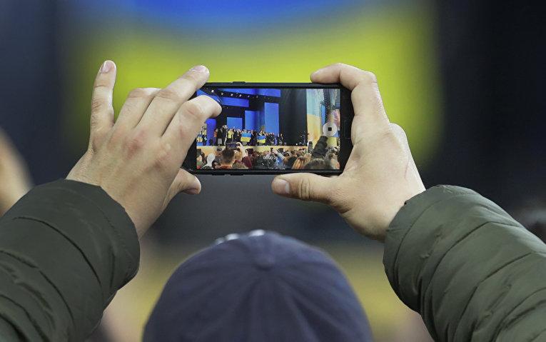 Мужчина фотографирует дебаты между Петром Порошенко у Владимиром Зеленским в Киеве