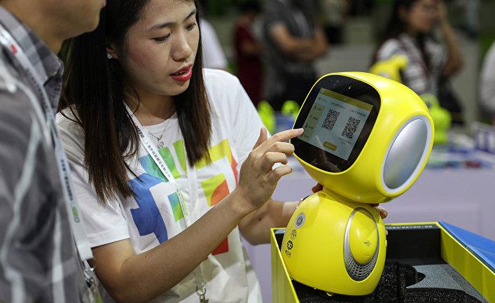 Посетители изучают робота на китайской международной выставке роботов в Шанхае