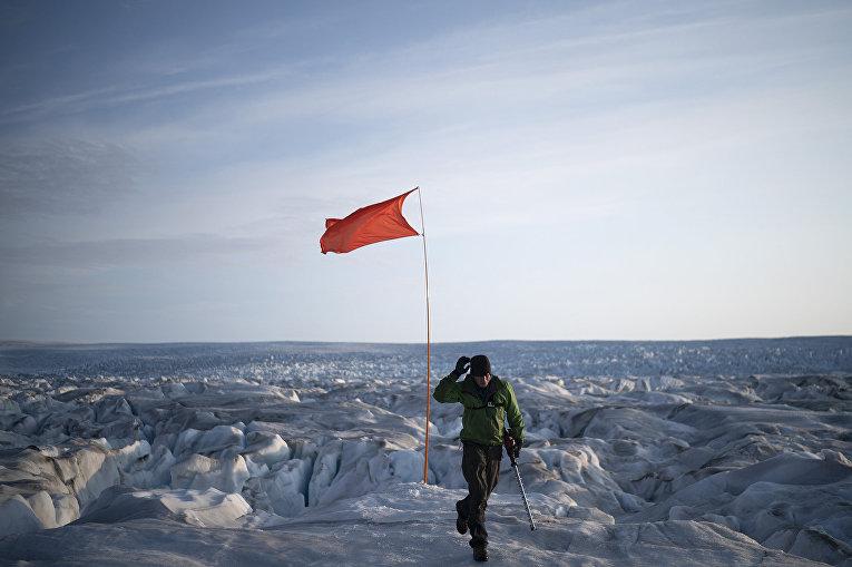 Офицер Брайан Ружо поднимает флаг нагренландском леднике Хельхейм