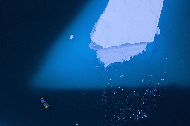15 августа 2019. Лодка проплывает мимо большого айсберга, Гренландия