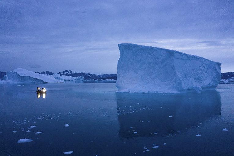 Лодка лавирует среди айсбергов, Гренландия