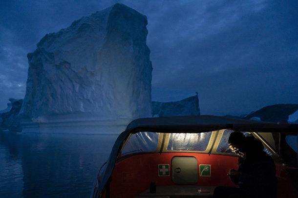 Лодка плывет мимо айсберга, Гренландия