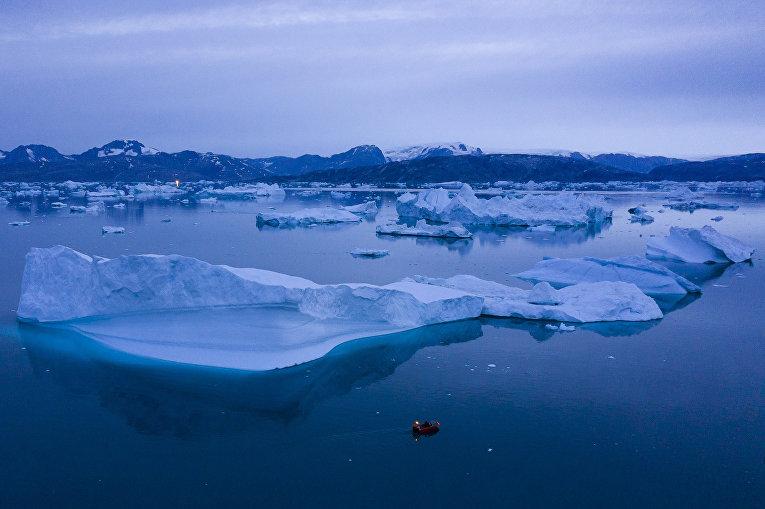 Лодка проплывает мимо айсбергов, Гренландия