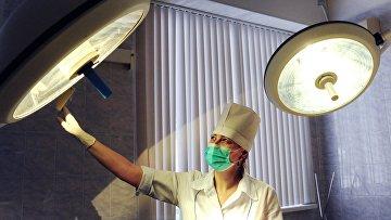 Медицинская сестра устанавливает свет в операционной