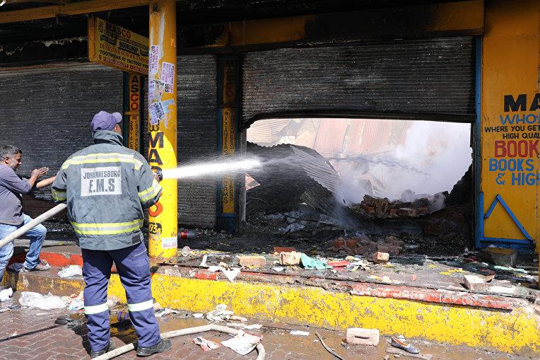 Пожарный заливает сгоревший магазин после ночных волнений, Йоханнесбург