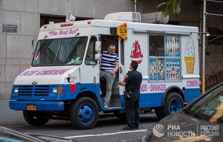 Сотрудник полиции общается с мороженщиком на улице в Нью-Йорке