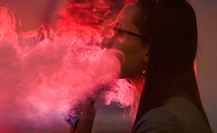 Девушка курит вейп