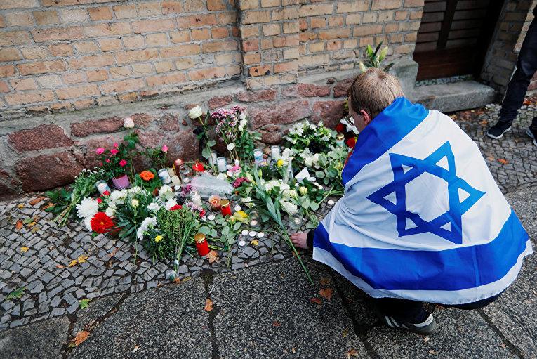 Человек с флагом Израиля возлагает цветы к месту стрельбы у синагоги в городе Галле, Германия