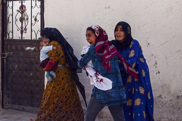 Женщины покидают дома в городе Акчакале во время обстрела