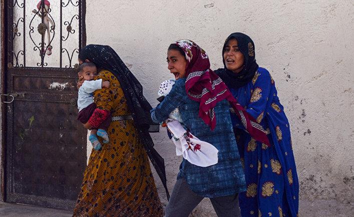 Женщины покидают свои дома в турецком городе Акчакале во время обстрела города