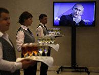 Официанты с шампанским у телевизора с трансляцией выступления Владимира Путина