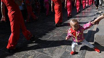 Прохожие наблюдают за костюмированным шоу на одной из улиц города Пинъяо