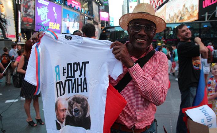 Мужчина на улице в Нью-Йорке демонстрирует футболку с изображением российского президента