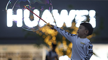 Мальчик играет с мыльными пузырями возле магазина Huawei в Пекине