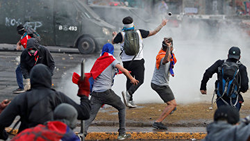 Участники антиправительственых протестов в Сантьяго, Чили