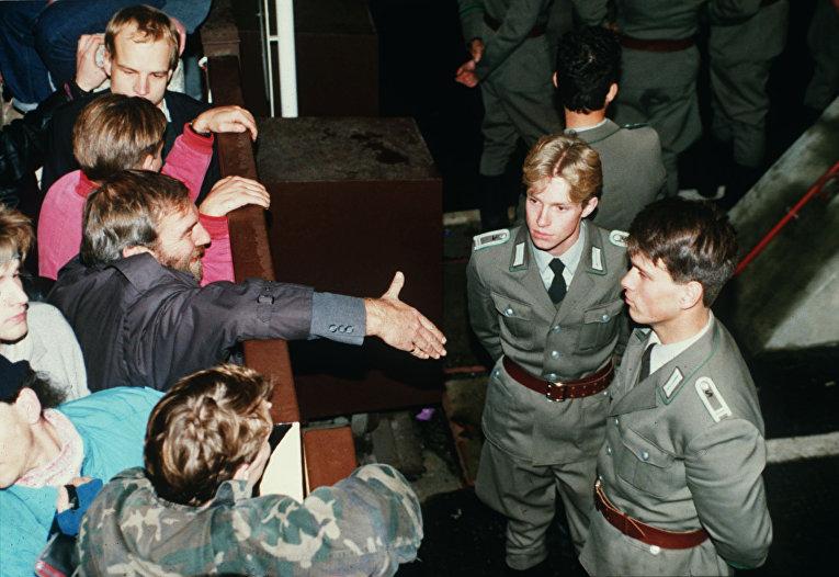 Восточногерманские пограничники отказываются пожать руку берлинцу на контрольно-пропускным пункте Чарли