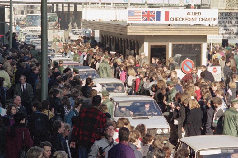 Граждане Восточного Берлина пересекают контрольно-пропускной пункт Чарли, чтобы посетить Западный Берлин в ноябре 1989 года