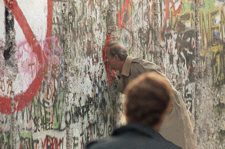 Госсекретарь США Джеймс Бейкер III смотрит через разлом в Берлинской стене на Потсдамской площади