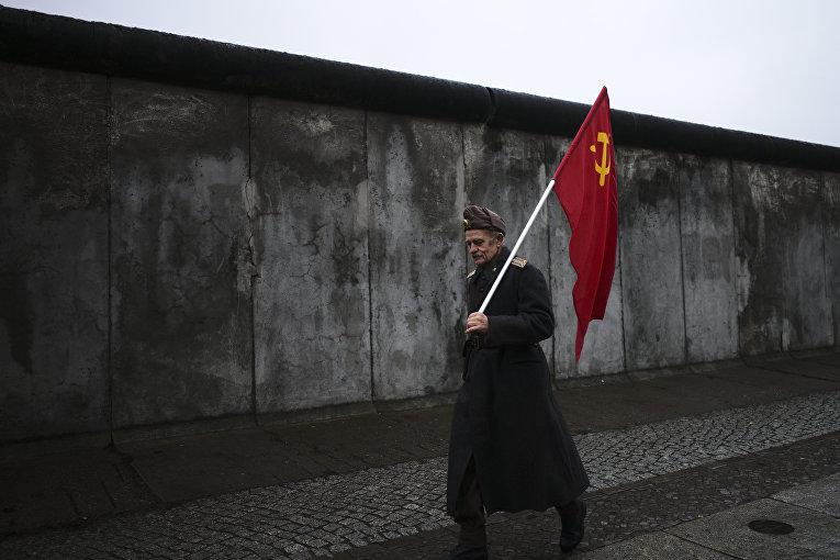 Пожилой человек с советским флагом на фоне Берлинской стены