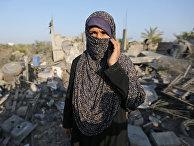 Женщина у разрушенного в результате израильского авиаудара дома в Секторе Газа