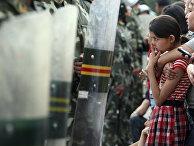 Уйгурская девушка возле полицейского оцепления в Урумчи, провинция Синьцзян, Китай