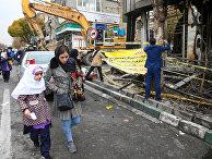 Люди в Тегеране идут мимо сгоревшего банка после протестов против повышения цен на топливо