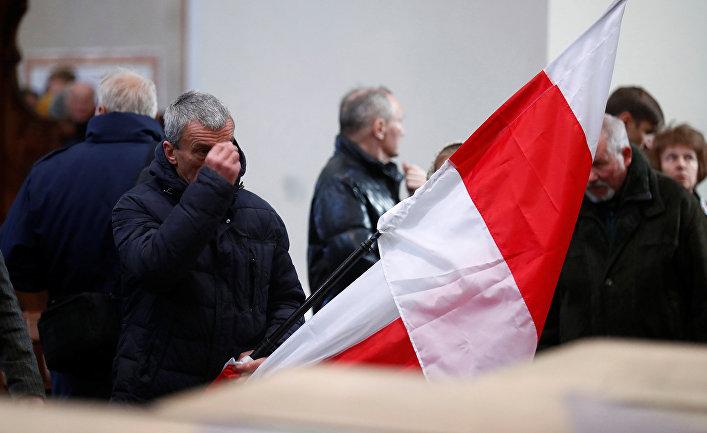 Мужчина держит польский флаг в Вильнюсе, Литва