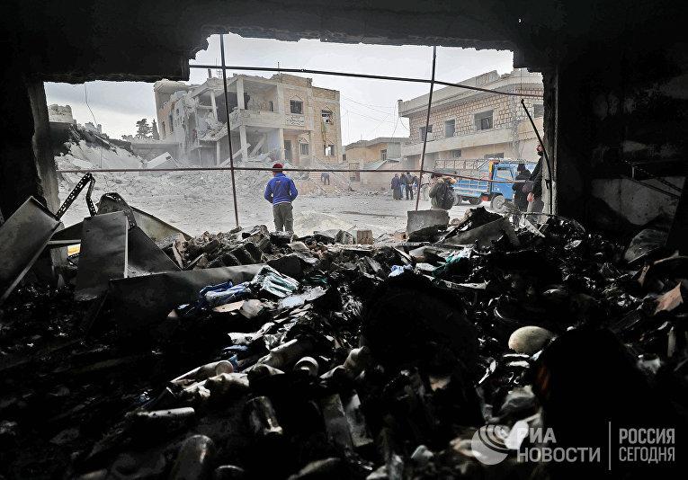 Сирийцы среди обломков после воздушных ударов в городе Кансафра на юге провинции Идлиб