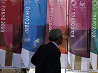 Мужчина проходит мимо баннеров Tokyo 2020