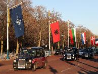 Лондонские такси проезжают мимо флагов в преддверии саммита НАТО в Лондоне, Великобритания