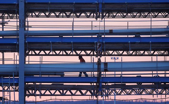 Строитель идет по мосту с трубопроводами на стройплощадке Амурского газоперерабатывающего завода, входящего в проект «Сила Сибири» Газпрома