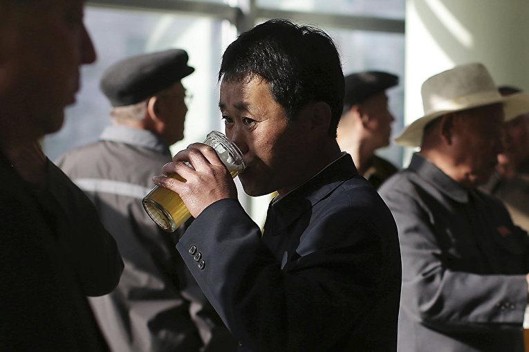 Мужчина пьет пиво в Пхеньяне, КНДР