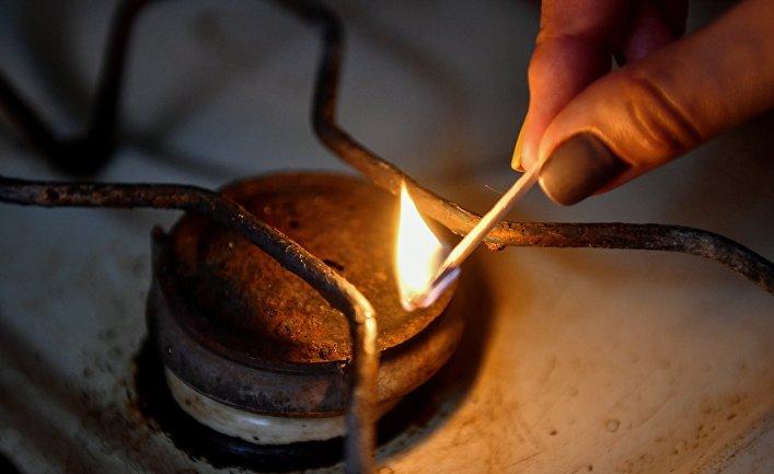 Женщина зажигает конфорку газовой плиты