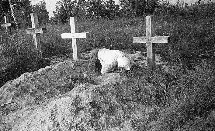 Женщина плачет на могиле своего близкого