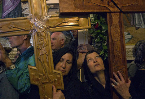 Православные христиане держат деревянные кресты в Иерусалимском храме
