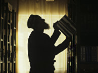 Пожилой таджик у книжных полок в своем доме