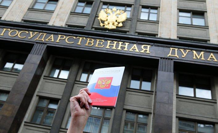 Конституция Российской Федерации на фоне здания Государственной Думы РФ в Москве