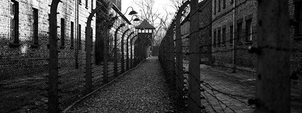 Путь к наблюдательной башне вдоль забора под напряжением из колючей проволоки в Освенциме, Польша