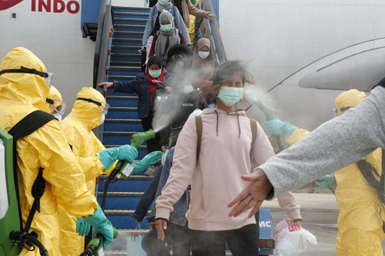 Медицинские работники распыляют антисептик для пассажиров рейса из Уханя в аэропорту Ханг Надим в Батаме, Индонезия