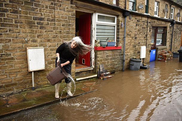 Женщина на затопленной улице в Мифолмройде, Великобритания