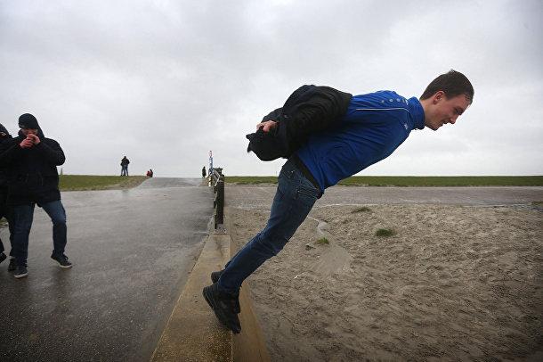 Мужчина балансирует на краю дамбы во время урагана Киара в Харлингене