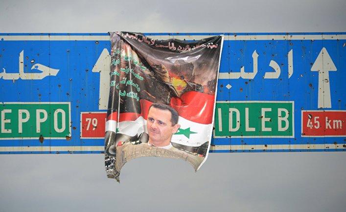 Плакат с портретом президента Сирии Башара Асада на дорожном указателе на город Идлиб в Сирии