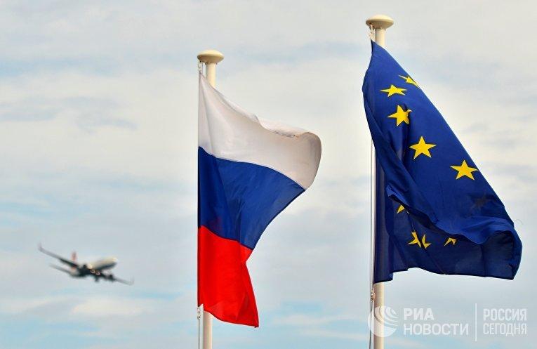 Флаги России, ЕС и Франции на набережной Ниццы. На дальнем плане - самолет заходит на посадку в международный аэропорт Ниццы.