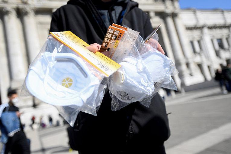 Уличный торговец продает медицинские маски у железнодорожного вокзала в Милане