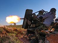 Сирийский боевик обстрелдивает позиции правительственных войск в провинции Идлиб