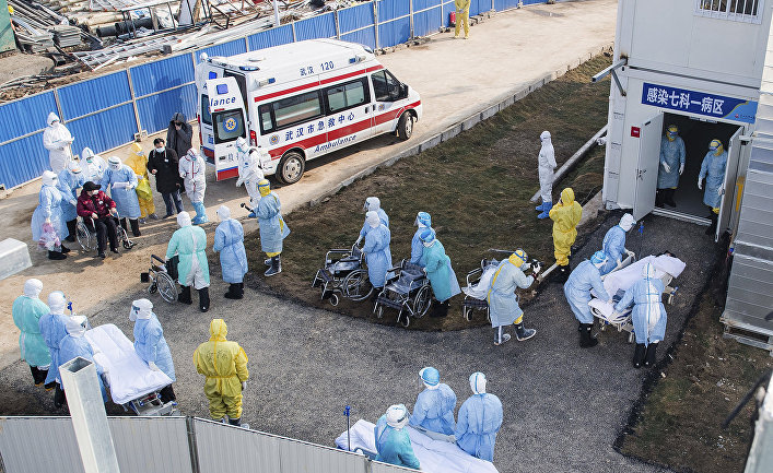 Медицинские работники в защитных костюмах в полевом госпитале в Ухане, Китай