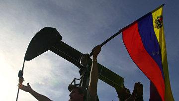 Флаг Венесуэлы у нефтяной вышки в Каракасе